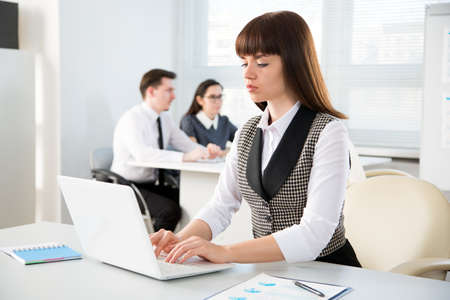 Young business woman with laptop in the office Stock Photo