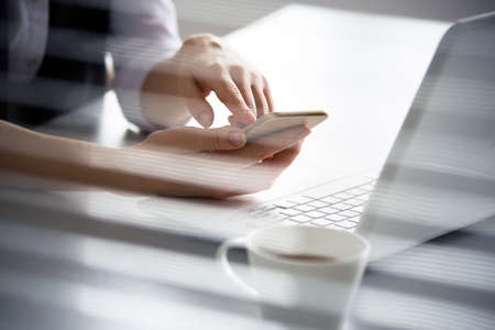 Business woman holding phone and using laptop. Online payment