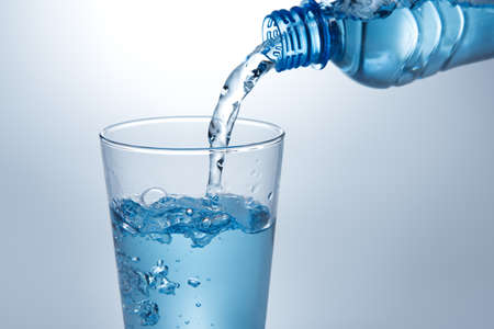 Pouring water from bottle into glass Stok Fotoğraf