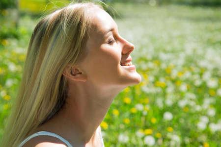 Beautiful young woman among dandelions Stock Photo