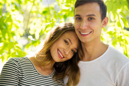Portrait of a happy couple hugging in a park in sunny day Stock Photo