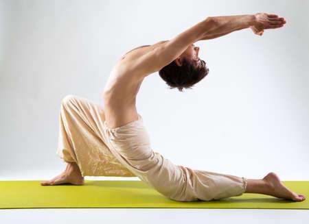 Young man with naked torso doing yoga