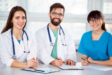 Group of doctors in clinic at workplace looking at camera and smiling