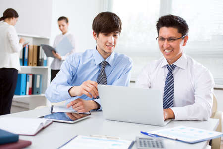 Two young businessmen discussing a new project at a meeting in the office Stock Photo