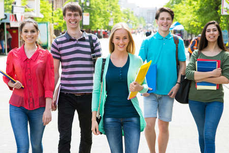 Full length of happy college students walking together Stock Photo
