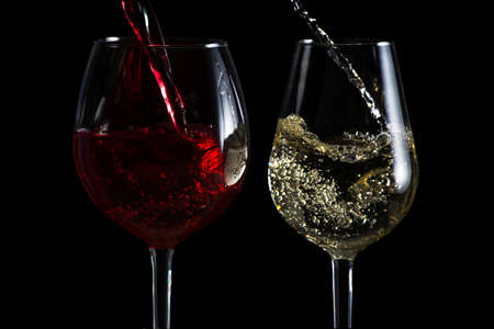 Schöner Spritzer Wein in einem Glas auf einem schwarzen Hintergrund Standard-Bild