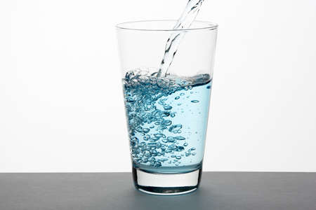 Beautiful splash of blue water in a glass