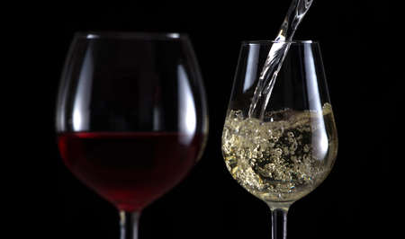 Beautiful splash of wine in a glass on a black background Stock Photo
