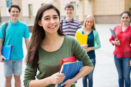 Female student outdoors with her friends Stock Photo