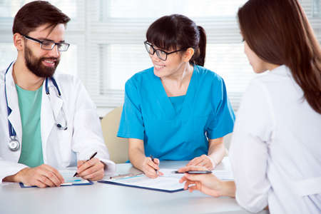 Group of doctors in the clinic discuss the diagnos of the patient
