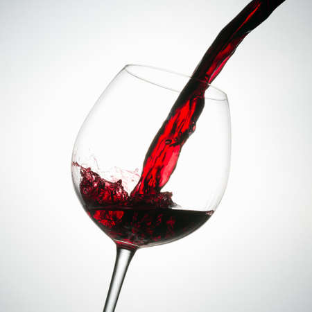 Beautiful splash of red wine in a glass on white background Stok Fotoğraf - 107646889