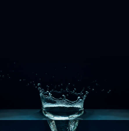 Beautiful splash of blue freshnes water isolated on a dark background