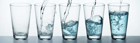 El juego de vasos se está llenando de agua.