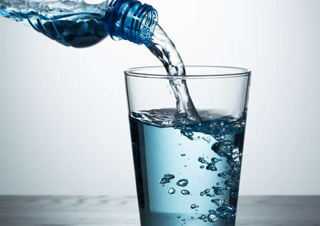 Pouring blue water from bottle into glass Stok Fotoğraf - 111479340