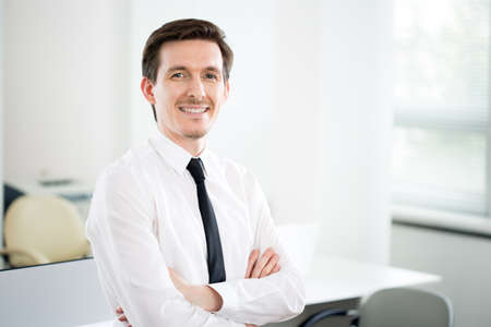 Portrait of young handsome businessman in a modern office Imagens
