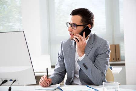 Junger gutaussehender Geschäftsmann, der in einem Büro telefoniert Standard-Bild