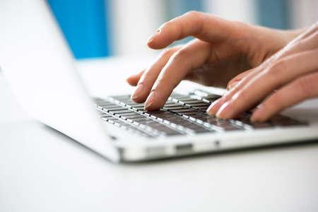 Primer plano de las manos de la empresaria escribiendo en una computadora portátil. Ver a través de las persianas