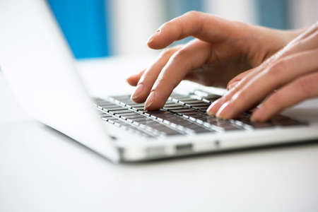 Primo piano delle mani della donna di affari che scrive su un computer portatile. Guarda attraverso le persiane