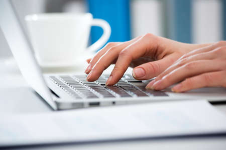 Close-up of hands of businesswoman typing on a laptop. View through blinds Imagens - 120595172