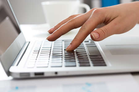 Close-up of hands of businesswoman typing on a laptop. View through blinds Imagens