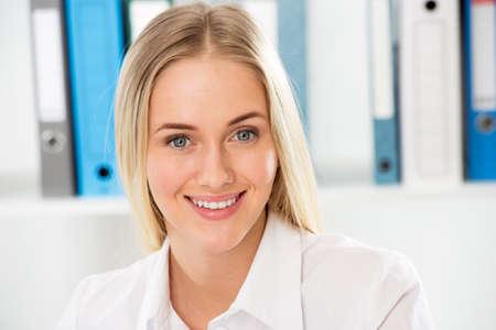 Portret van een glimlachende jonge aantrekkelijke zakenvrouw in een kantoor