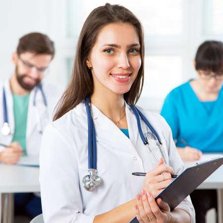 Retrato de una joven doctora en una clínica con colegas en el fondo Foto de archivo
