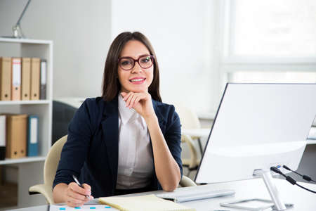 Mujer de negocios hermosa joven con la computadora en una oficina