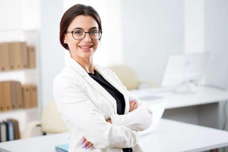 Portret uśmiechniętej młodej atrakcyjnej kobiety biznesu w biurze