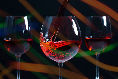 Beautiful splash of red wine in a glass on a dark background