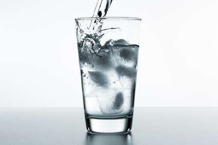 Bella spruzzata di acqua blu in un bicchiere con ghiaccio Archivio Fotografico