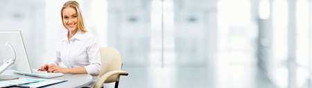 Portrait of a young business woman using computer at office. Panoramic image Stock Photo