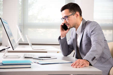 Young handsome businessmantalking on the phone in an office Foto de archivo - 122504875