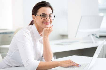 Junge Geschäftsfrau in einem Büro lächelnd in die Kamera schaut