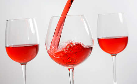 Beautiful splash of red wine in a glass on a white background