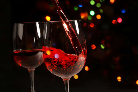 Beautiful splash of red wine in a glass on the background of festive lights
