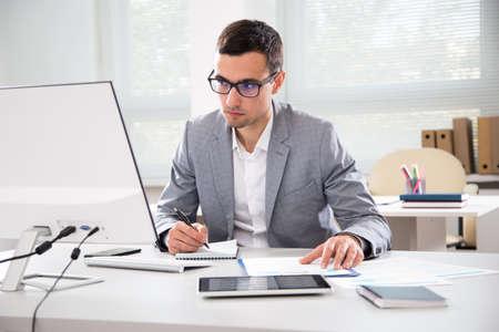 Ernster Geschäftsmann, der mit Computer in einem Büro arbeitet