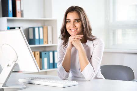 Hermosa joven empresaria con computadora en una oficina. Foto de archivo