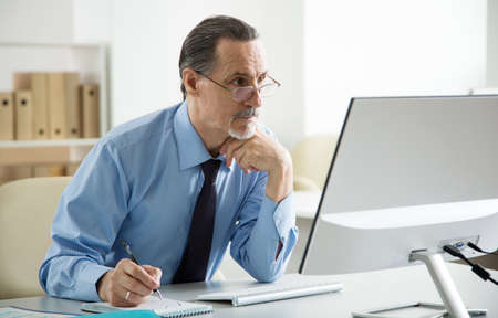 Portrait of senior businessman using computer in an office