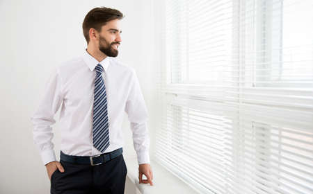 Young businessman stands by the window in the office