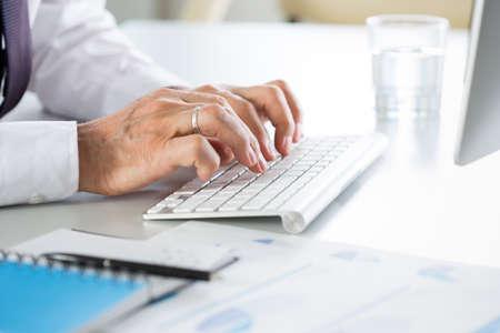 Close-up van zakenmanhanden die op het toetsenbord op de werkplek in een kantoor typen