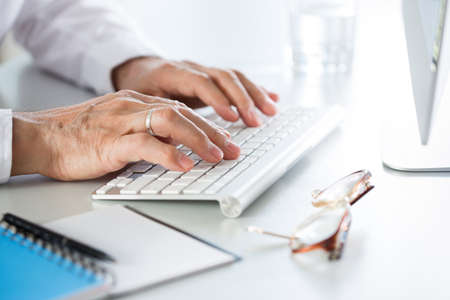 Close-up of businessman hands typing on the keyboard at the workplace in an office