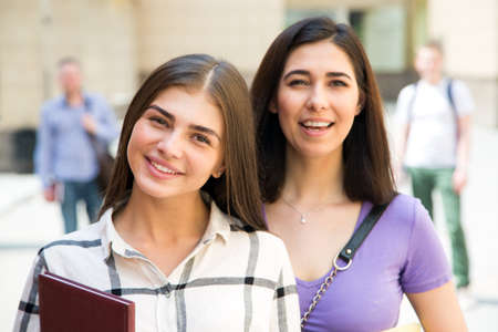 Portrait of a female students outdoors with friends Imagens