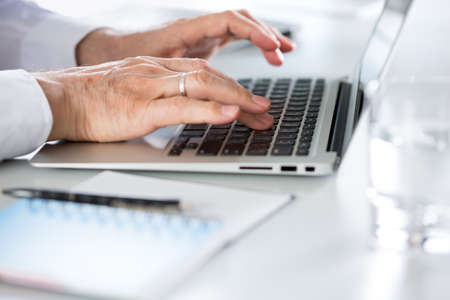 Closeup of businessmans hands working with laptop in an office Zdjęcie Seryjne