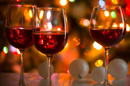 Crystal glasses of wine and Christmas balls on the background of Christmas lights Stock Photo