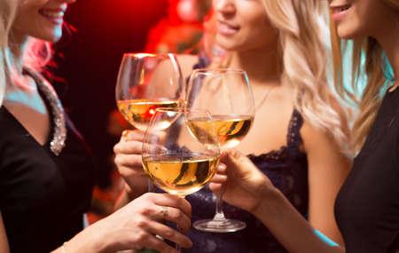 Ragazze splendidamente vestite con bicchieri di vino a una festa di Natale Archivio Fotografico