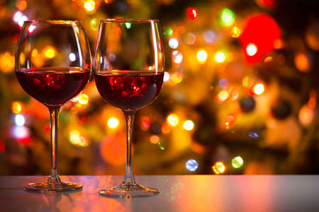 Copas de vino de cristal en el fondo de las luces de Navidad