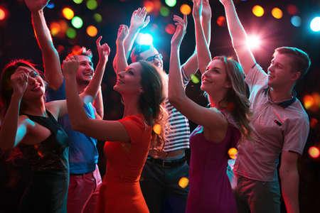 Groep gelukkige jonge mensen die plezier hebben met dansen op een feestje. Stockfoto