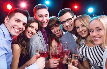 Feliz grupo de jóvenes amigos tocando las copas entre sí