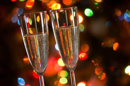 Copas de champán en el fondo de las luces de Navidad Foto de archivo