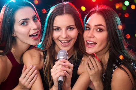 Szczęśliwe dziewczyny bawią się śpiewając na imprezie Zdjęcie Seryjne